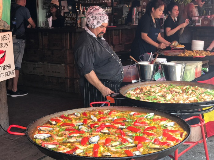 The big pans of paella with the chef